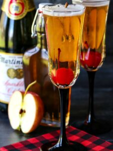 Apple cider cocktails with cherries and sparkling cider bottle