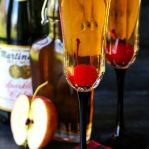 Apple cider cocktails with cherries and sparkling cider bottle