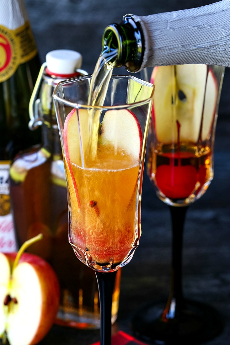 pouring sparkling cider into an apple cider cocktail