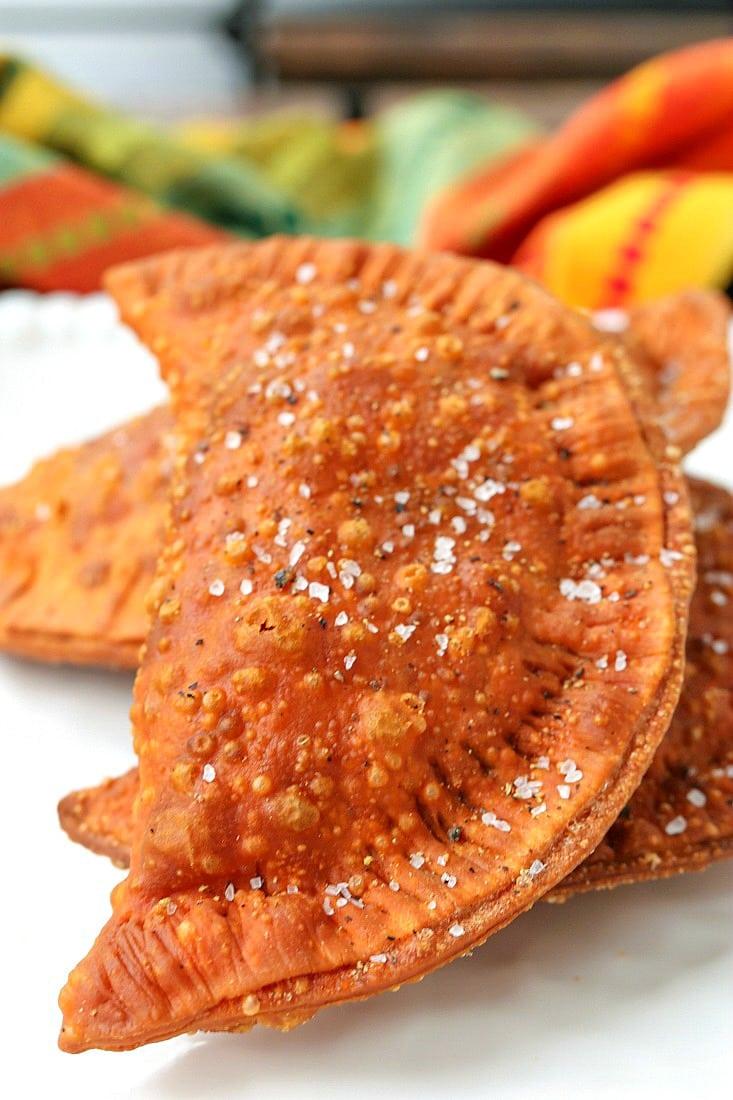 beef empanadas on a platter with salt