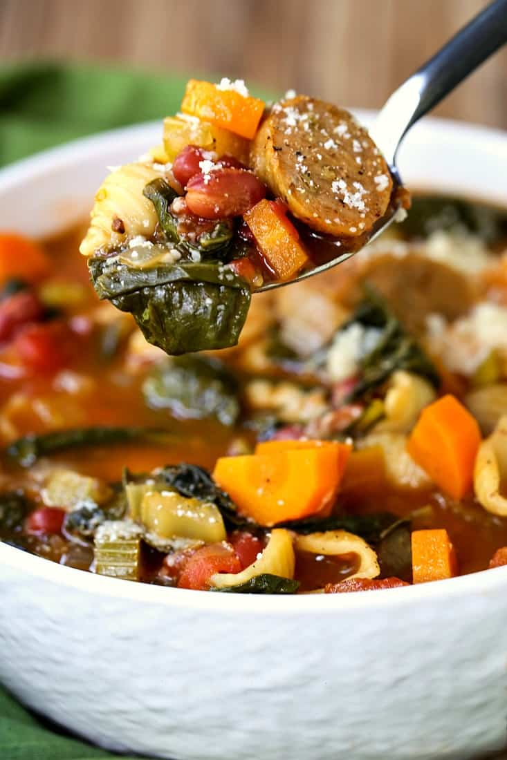 A spoon with sausage minestrone soup