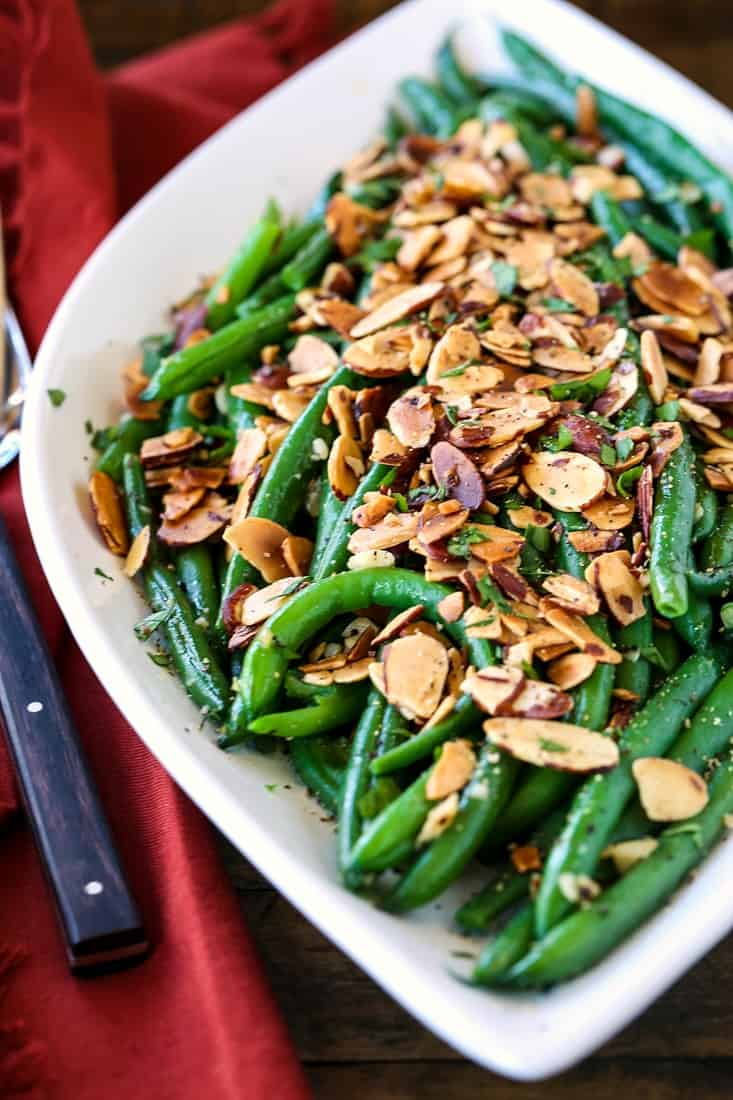 green beans with sliced almonds on a white platter with forks