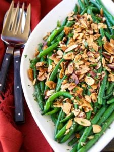 green beans almondine on a white platter