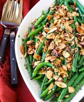 green beans almondine on a white platter