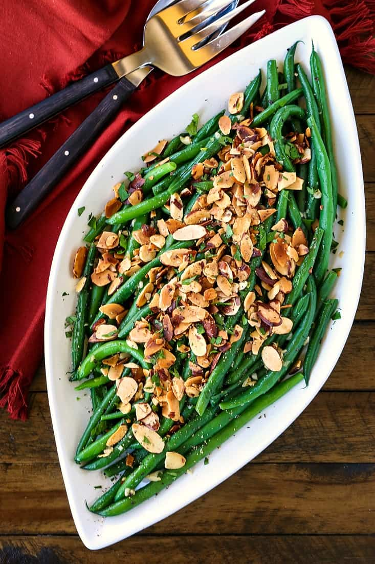 Green beans on a platter with sliced almonds and maroon napkin
