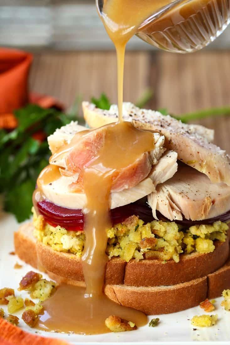 Turkey gravy pouring over open face turkey sandwich