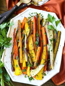 Roasted carrots with parsley on a white platter