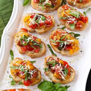 Bruschetta recipe on a white platter with parmesan cheese and basil