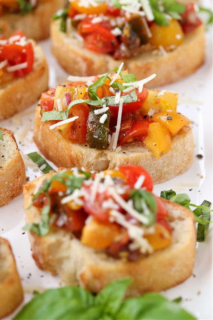 Tomato bruschetta on a platter with basil