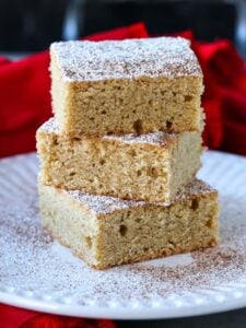 Eggnog Cookie Bars stacked on white plate with powdered sugar