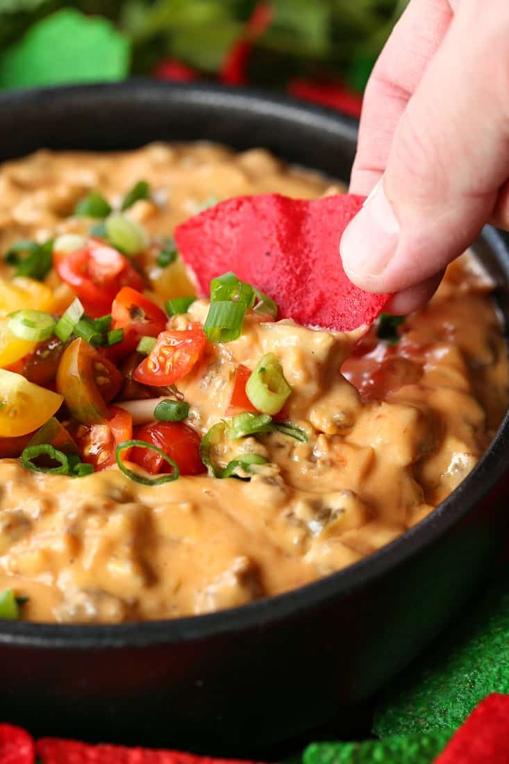 Sausage queso dip with tortilla chip dipping in