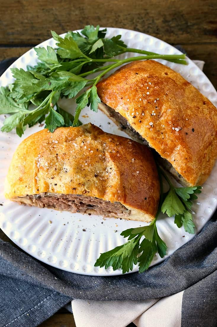 Individual Beef Wellington on white plate with parsley