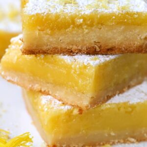 Lemon bars made with Limoncello stacked on white plate