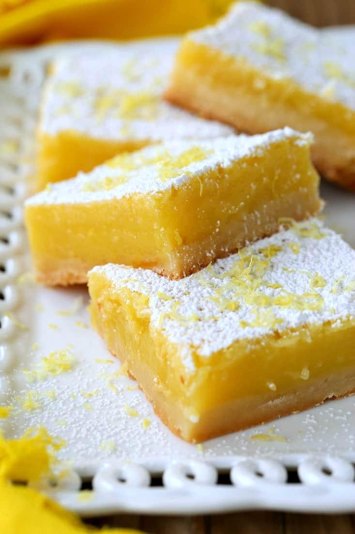 Lemon Bars stacked on platter with yellow napkin