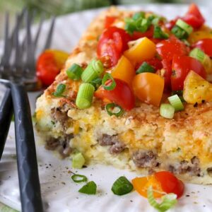 Sausage Breakfast Casserole on plate with tomatoes and scallions