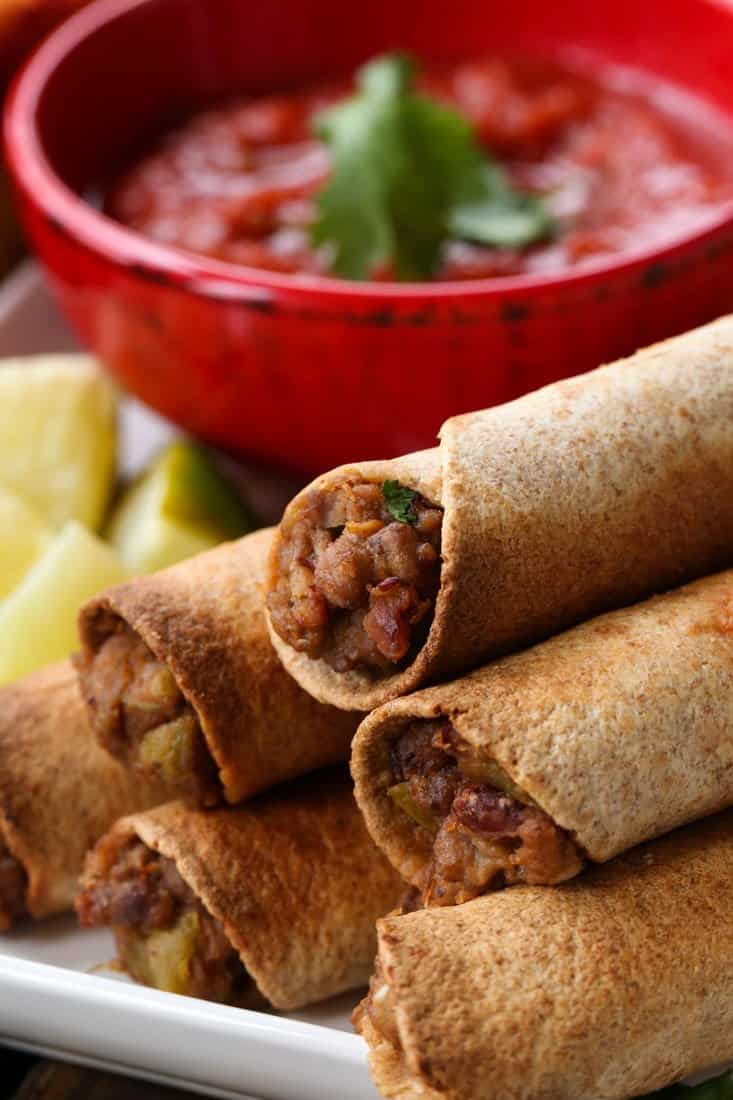 Crispy beef taquitos stacked on a plate