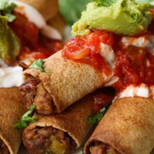 Homemade beef taquitos with sour cream, salsa and guacamole toppings