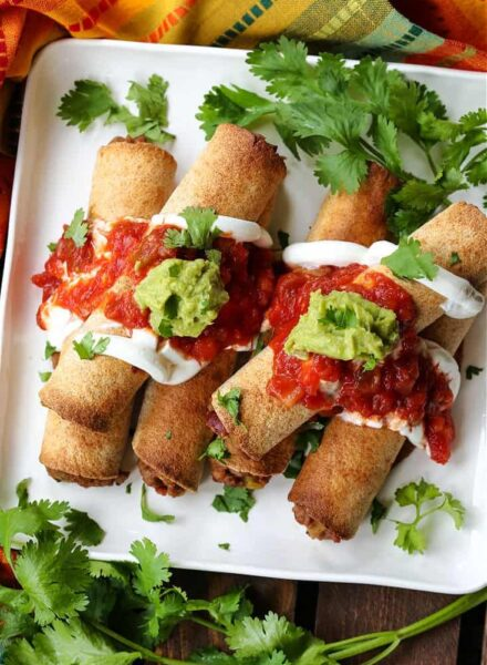 air fryer beef taquitos on a plate with salsa and guacamole