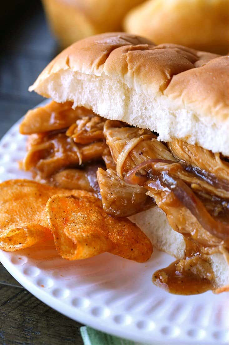 sweet pulled chicken on a roll with chips on the side
