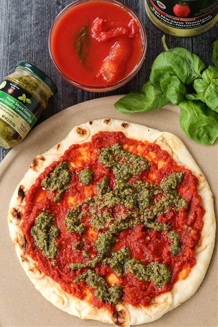 Pizza with sauce and basil pesto
