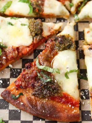 Slice of Sausage Pesto Pizza drizzled with olive oil