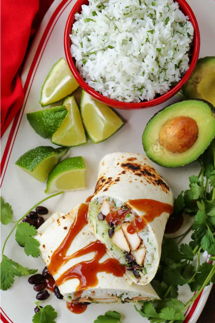 Chicken Burritos sliced on a plate with avocado and rice