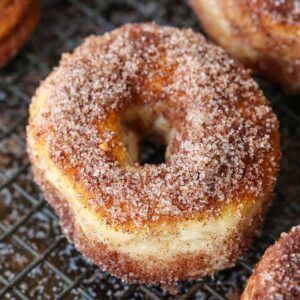 Cinnamon sugar donuts on baking rack to dry