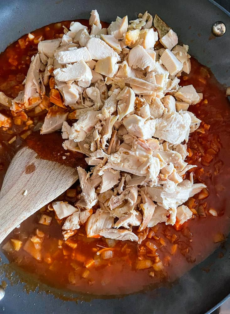 chicken and sauce in a pan for chimichanga filling