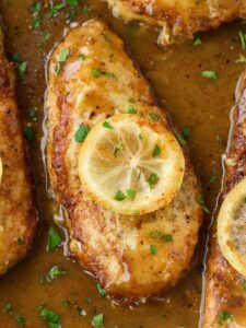 Chicken francese in a pan with a slice of lemon