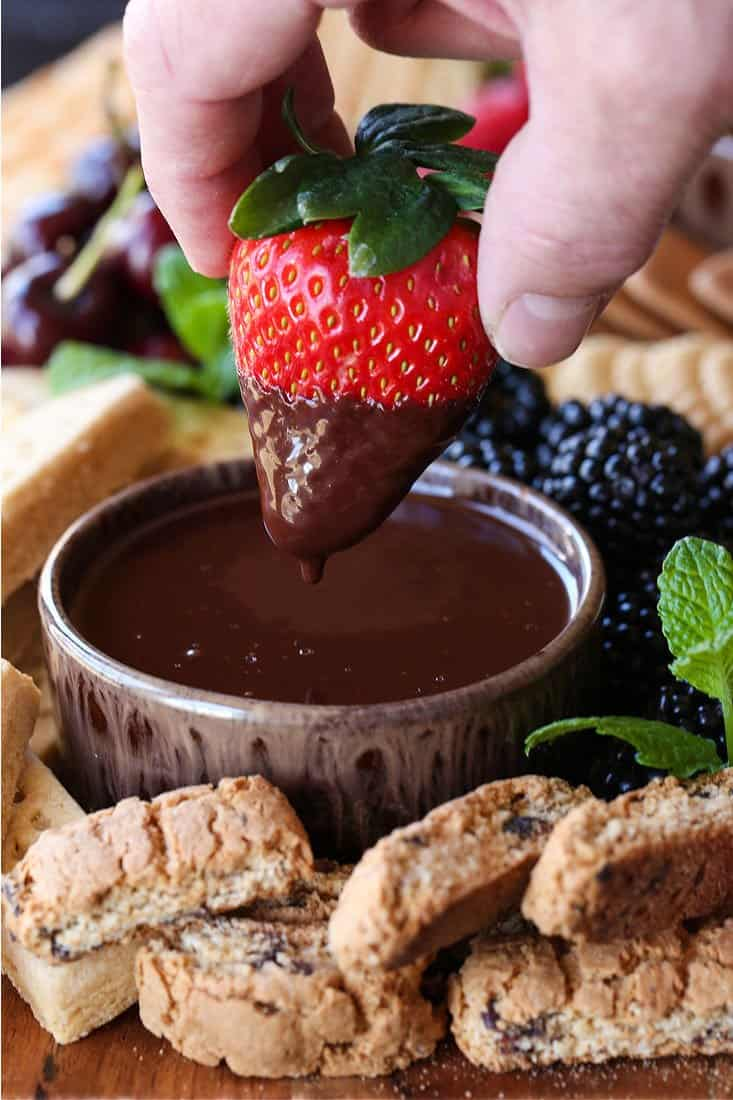Strawberry being dipped into Chocolate Fondue