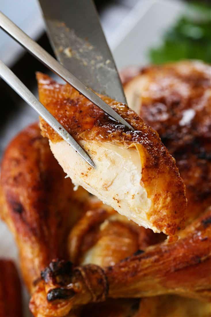 Slice of roast chicken on a serving fork
