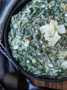 Creamed Spinach in a black bowl with parmesan cheese
