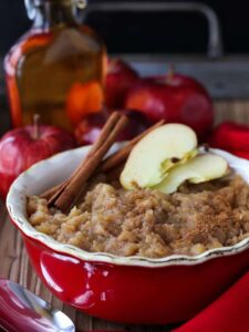 Homemade applesauce in a dish with cinnamon sticks