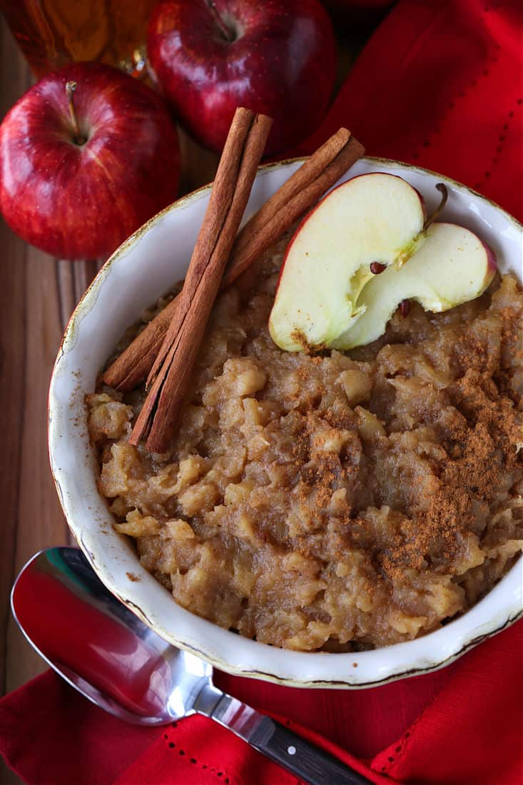 Bourbon applesauce in a red bowl with sliced apples
