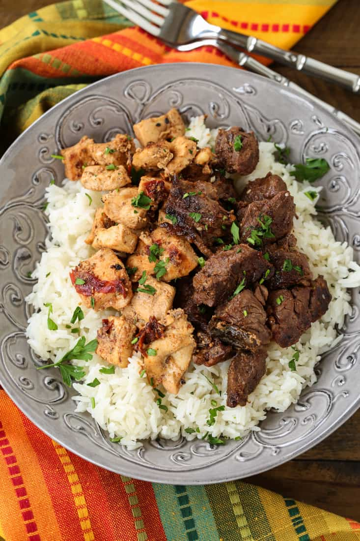 Marinated chicken and steak in a bowl with rice