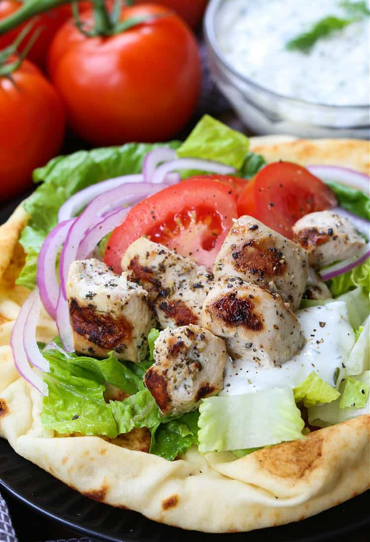 chicken souvlaki on pita bread with tomatoes, onions and tzatzikki sauce