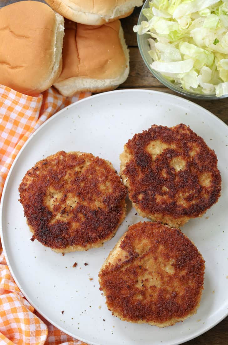 Chicken patties on a plate with buns and lettuce