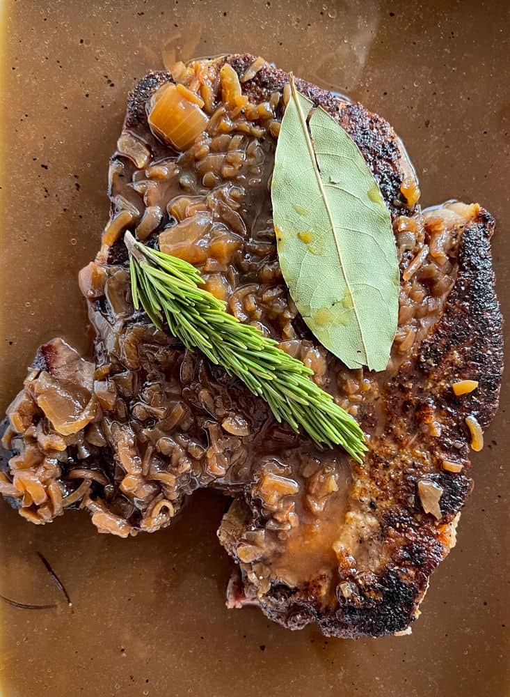 Chuck roast, rosemary and bay leaf in gravy for slow cooker beef recipe