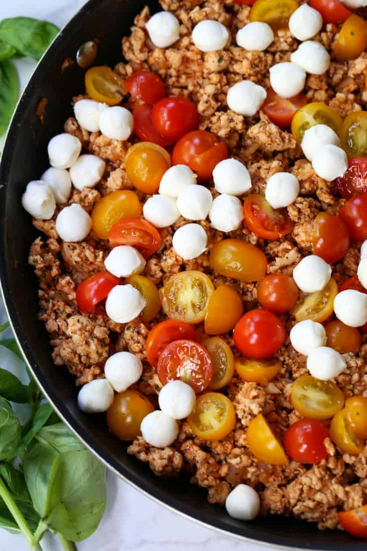 Ground chicken recipe in a skillet with mozzarella cheese and tomatoes