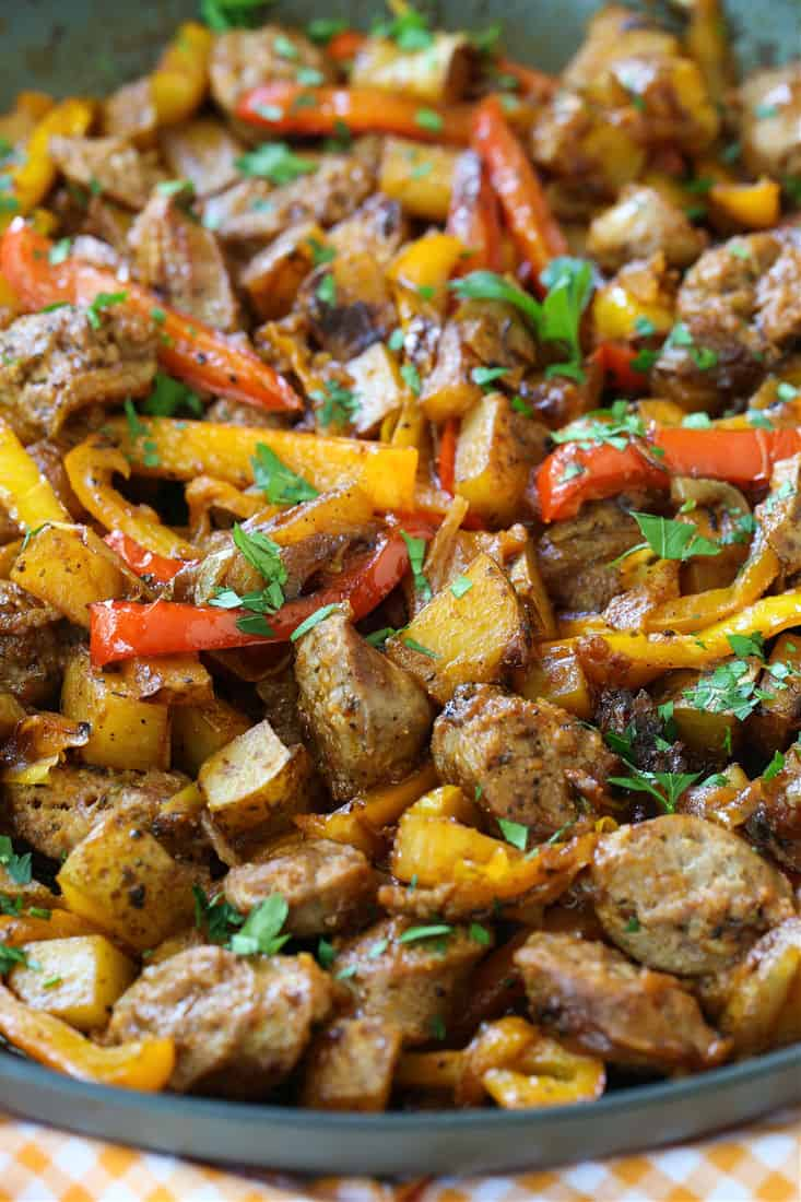 Italian sausage and potatoes tossed with peppers in a skillet