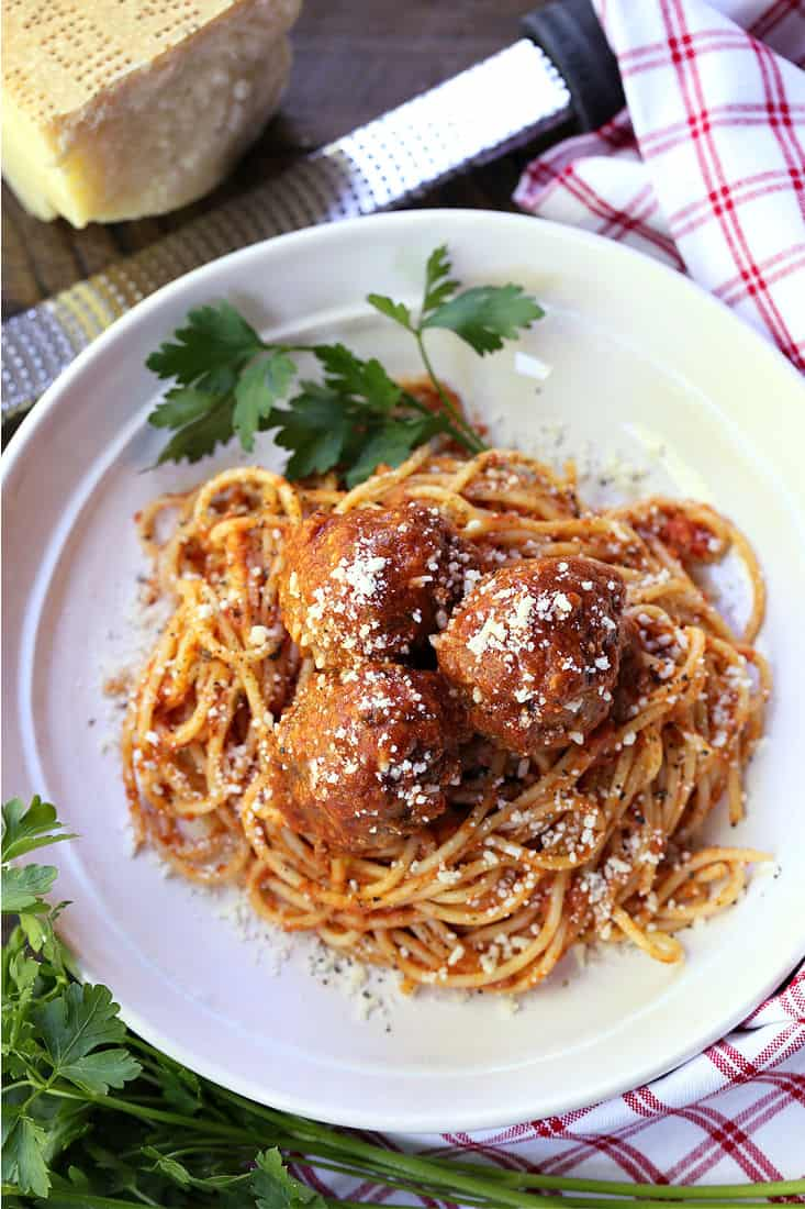 Spaghetti and meatballs on a white plate with parlsey