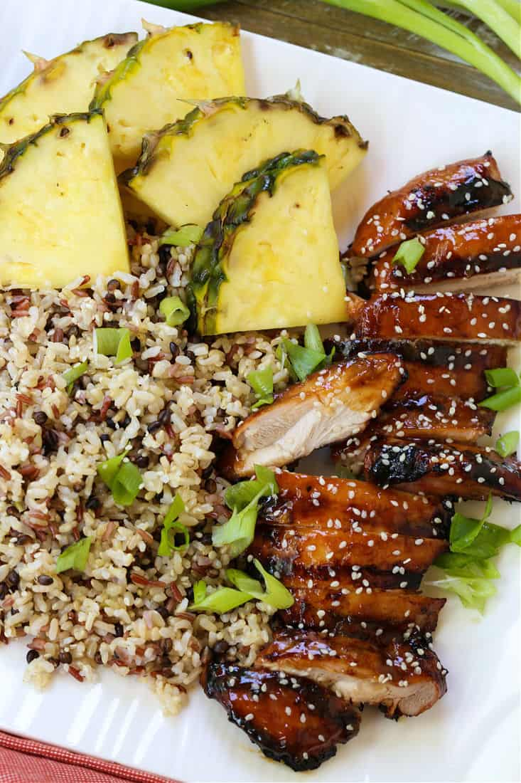 grilled chicken teriyaki on a platter with rice and pineapple