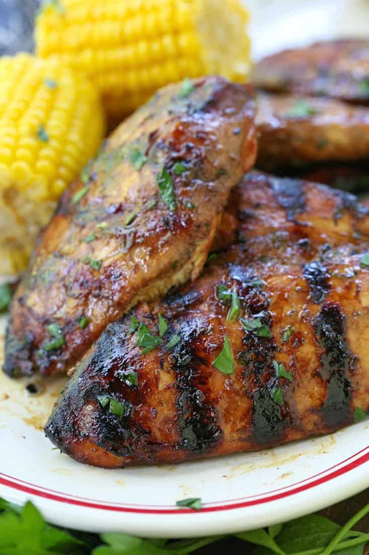 Grilled chicken breast recipe on a plate with corn