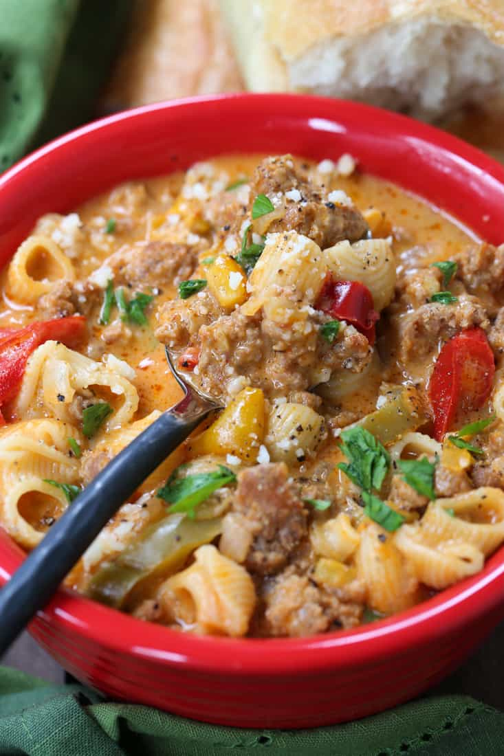 Soup recipe with sausage and pasta in a bowl with spoon