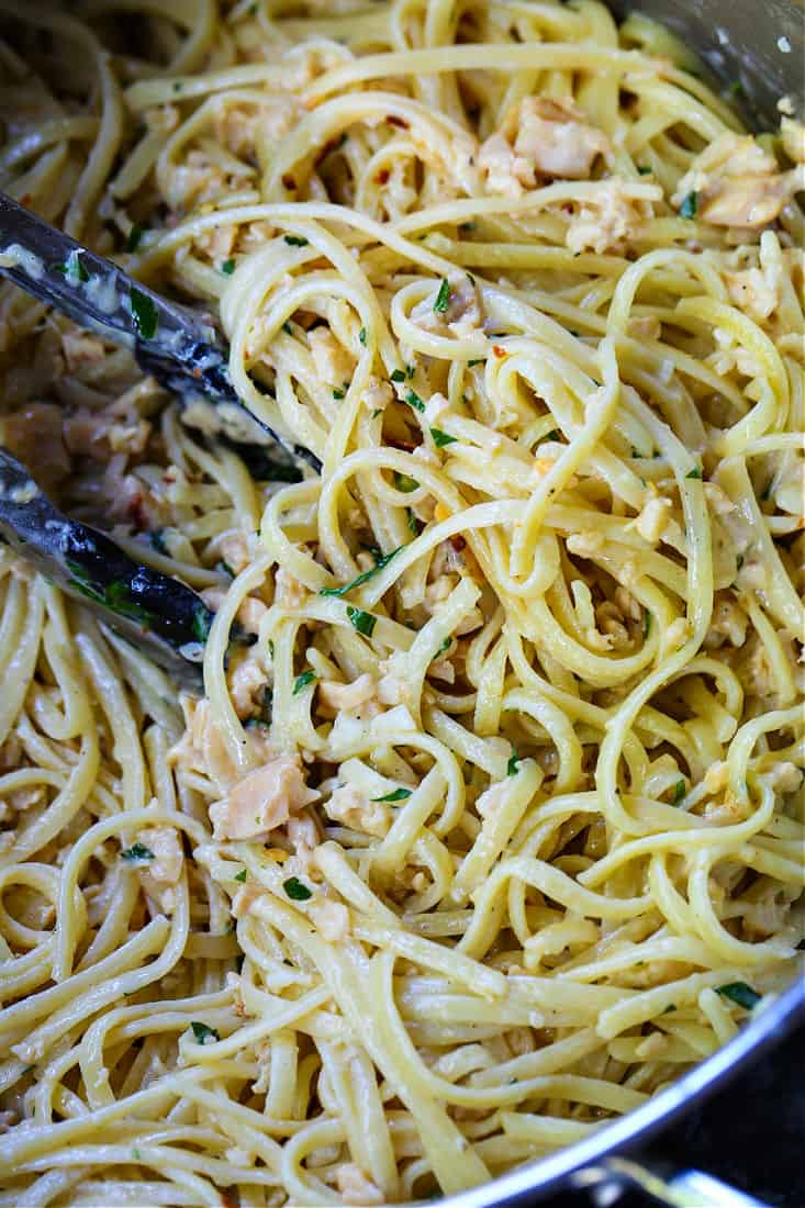linguine with clams in a pot with tongs
