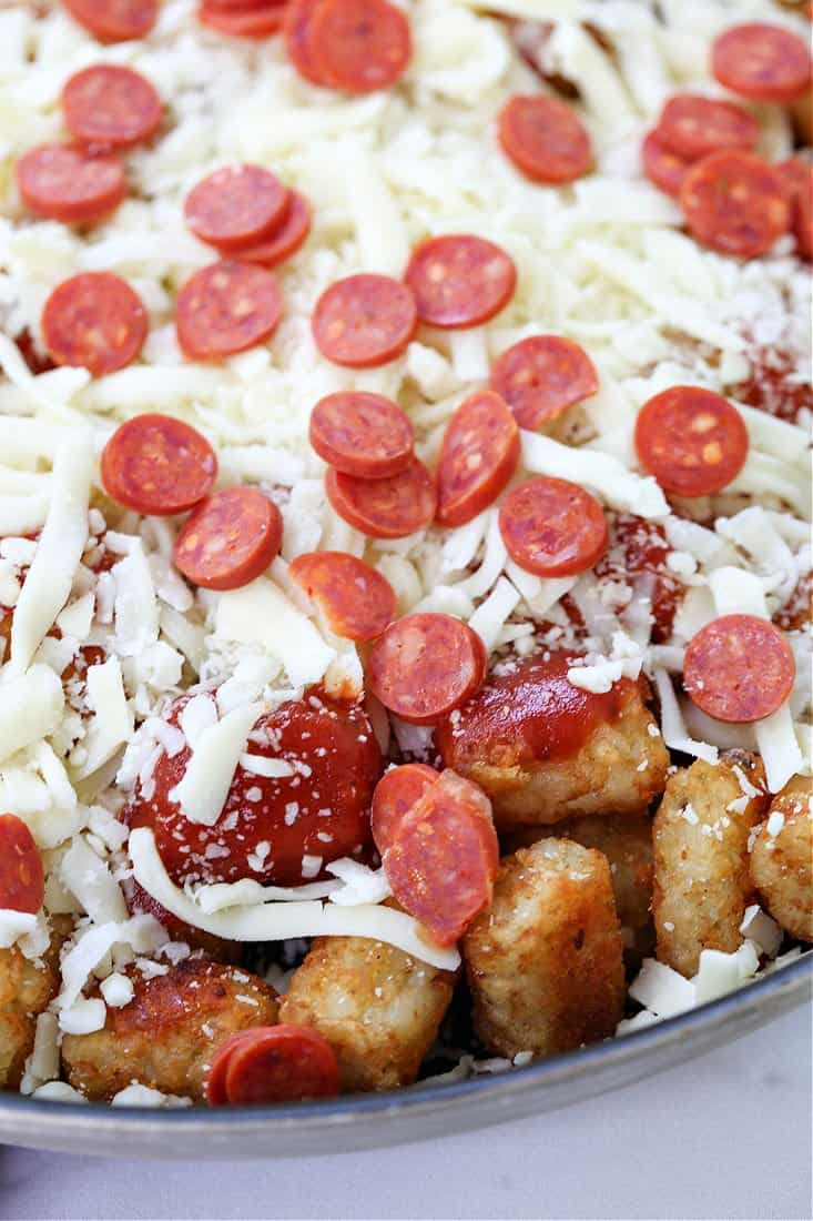 Pile on all your favorite pizza toppings when your making these fun Pepperoni Pizza Totchos! before going into the oven