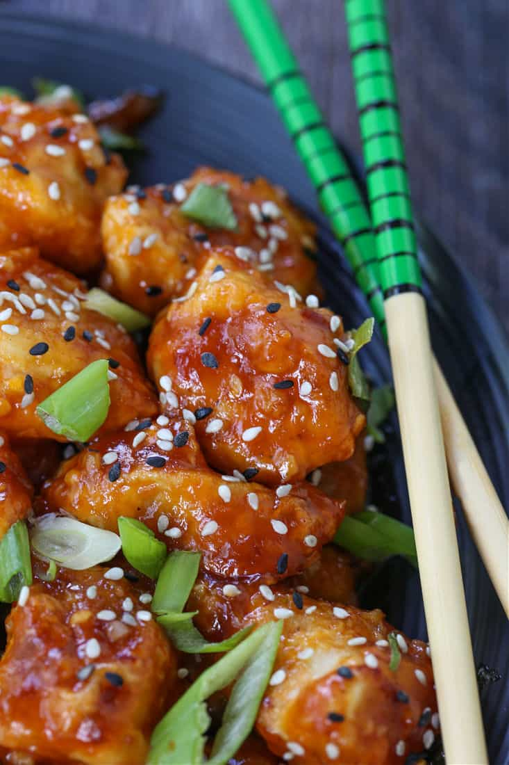General Tso's Chicken on a black plate with chop sticks