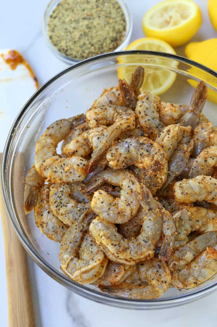 Shrimp in a bowl with lemon pepper seasoning and fresh lemons