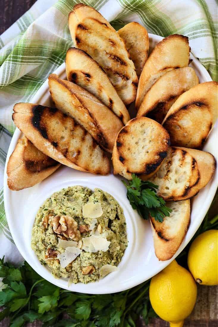 Artichoke Walnut Pesto on a platter with toasted crostini