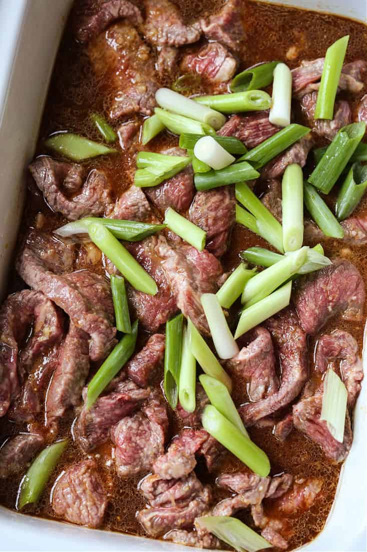 Sliced steak in a crock pot with scallions